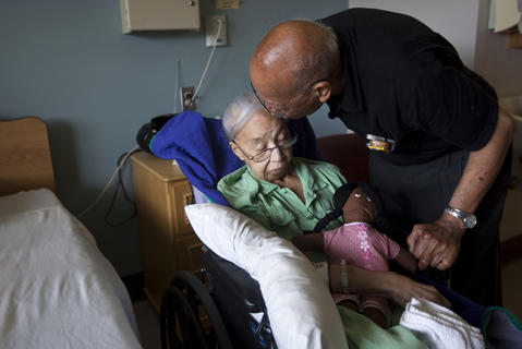 "Photo Of The Week: July 13-July 19, 2013   Jap Curry kisses his wife Sadie Curry before departing an assisted living center in Hampton on July 12. Jap visits Sadie, who has Alzheimer's disease, every morning and feeds her lunch. After singing and playing his old jazz recordings during recent visits, Jap says he has seen some reaction from his wife of 70 years. ""I always told her the name of the song that I was playing,"" he said. ""But a month ago, I told her that this next song is 'I Just Want to Hold Your Hand.' She said, 'You can hold my hand if you want to.'"""