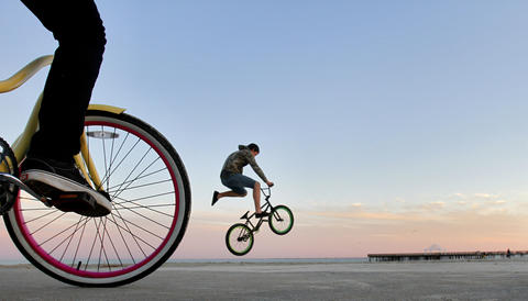 "Hunter Mallinson, 15, of Hampton practices bike tricks along the sea wall at Buckroe Beach Wednesday evening. ""After spending most of the day confined to sitting in a chair while waiting for a car repairs, I embraced the opportunity to find a feature Wednesday afternoon. Having just moved to Newport News from Michigan less than two weeks ago, I set out to look in area that I hoped would give a few different possibilities. In Buckroe Beach, I found people walking in the sand, exercising, and finally a group of teenage boys riding their bicycles along the seawall. I laid on the ground next to a boy on his bicycle and waited for another boy to come into the frame while doing a trick."""