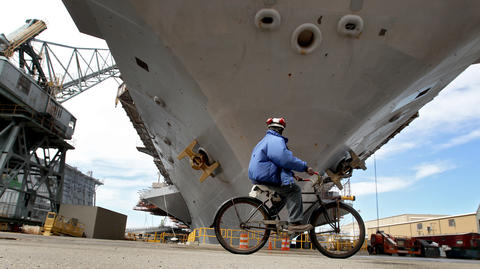 "A shipyard employee rides past the carrier USS Lincoln in dry dock 11 at Newport News Shipbuilding Monday morning. The ship will take about four years to refuel and update systems. ""Making a little something out of nothing should be the title of this photo. The assignment was sold as a tour of the USS Lincoln at the Newport News shipyard but turned out to be a press conference with people talking about the ship and the repair work to be done. Photogs hate talking head photos so I began walking around the bow of the ship looking for something to shoot. Shipyard workers use bicycles to get around on the massive facility and every now and then the odd worker would ride by. What I like about this photo is the sense of scale. It's a massive ship up close."""