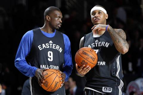 Luol Deng talks with forward Carmelo Anthony during practice.