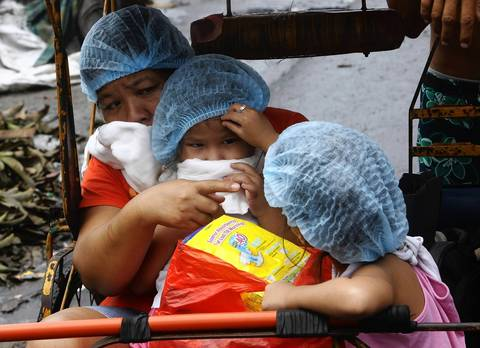 A mother and her two daughters cover their faces with towels because of the stench on the road after a typhoon battered Tacloban in the Philippines.