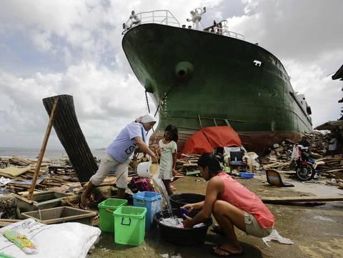 Filipino women wash clothes next to a ship washed ashore in Tacloban.
