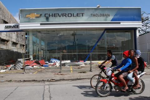 Residents ride past a damaged car dealership in the aftermath of Typhoon Haiyan on Nov. 10.