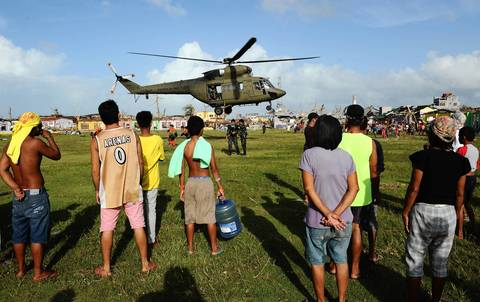 Residents watch as a military chopper hovers in Guiuan town, Eastern Samar in the Philippines.