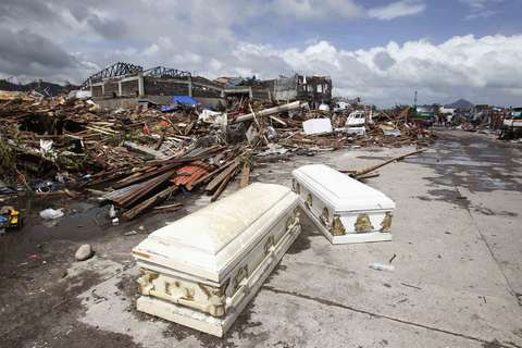 Empty coffins lie on a street near houses damaged after super Typhoon Haiyan battered Tacloban city, central Philippines, on Nov. 10.