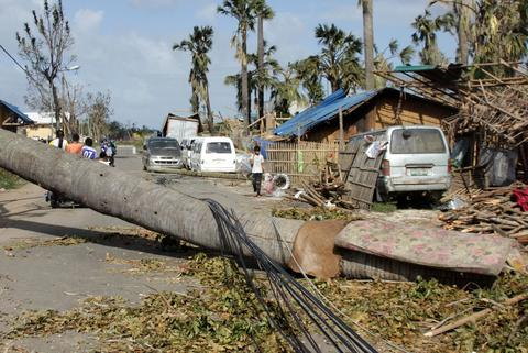 People walk amongst debris and damaged houses in the aftermath of Typhoon Haiyan in Iloilo on Nov. 10.