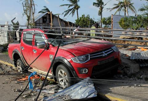 A damaged vehicle and houses in the aftermath of Typhoon Haiyan in Iloilo on Nov. 10.