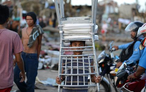 A child carries a chair from a hotel in Palo on Nov. 10, three days after devastating Typhoon Haiyan hit the area.
