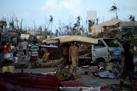 Residents carry a mattress from a hotel in Palo, eastern island of Leyte on Nov. 10.