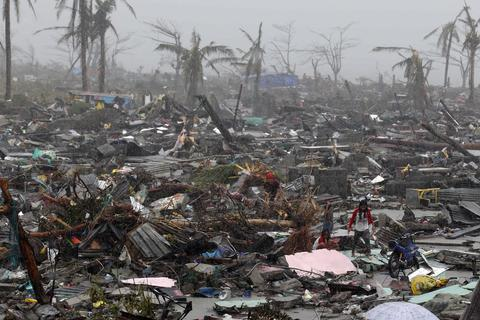 Filipino villagers look for belongings during a heavy downpour amidst houses damaged in the super typhoon devastated city of Tacloban, Leyte province, Philippines on Nov. 10, 2013