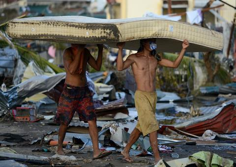 Residents carry a mattres from a hotel in Palo on Nov. 10, 2013, three days after devastating Typhoon Haiyan hit the area.
