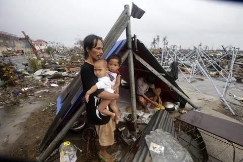 A Filipino father and his children wait for food relief outside their makeshift tent in the super typhoon devastated city ofTacloban, Leyte province, Philippines on Nov. 10, 2013.