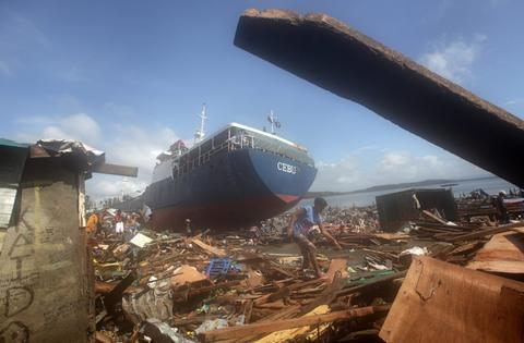 A Filipino woman walks by a ship washed ashore in the super typhoon devastated city of Tacloban, Leyte province, Philippines on Nov. 10, 2013.
