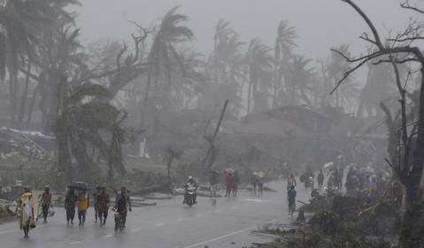 Survivors walk on a road amidst heavy downpour after Typhoon Haiyan battered Tacloban city in central Philippines November 10, 2013.