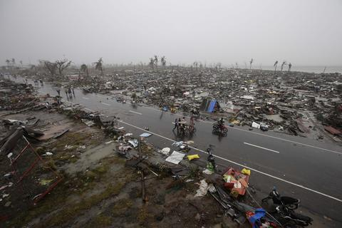 Filipino villagers carry their belongings during a heavy downpour walk past rubble of houses in the super typhoon devastated city of Tacloban, Leyte province, Philippines on Nov. 10, 2013.