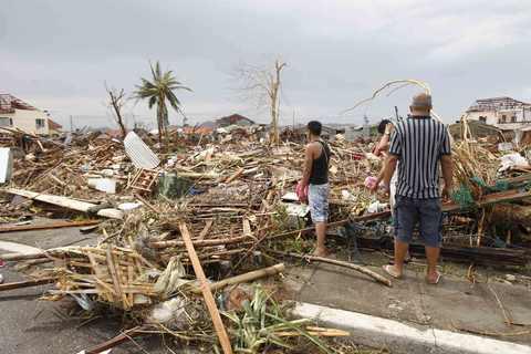 Survivors assess the damage after super Typhoon Haiyan battered Tacloban city, central Philippines, on Nov. 9.