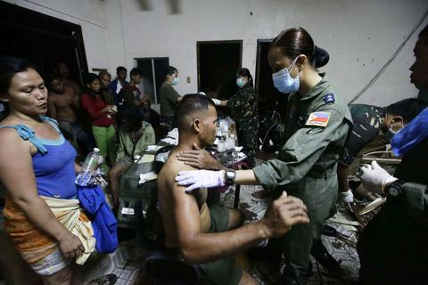Medical soldiers treat wounded victims after super Typhoon Haiyan battered Tacloban city, central Philippines, on Nov. 9.