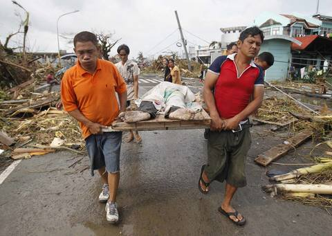 Survivors carry a person killed after super Typhoon Haiyan battered Tacloban city, central Philippines, on Nov. 9.