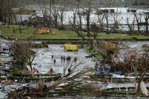 People walk among debris of fallen trees at Tacloban airport in the aftermath of Super Typhoon Haiyan in Tacloban, eastern island of Leyte on Nov. 9.