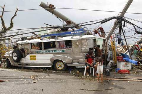 Survivors who lost their homes use a Jeepney public bus as shelter after a super Typhoon Haiyan battered Tacloban city, central Philippines, on Nov. 9.