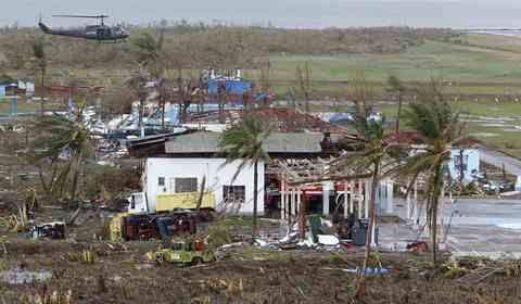 A helicopter hovers above damaged houses near the airport after super Typhoon Haiyan battered Tacloban city, central Philippines, on Nov. 9.