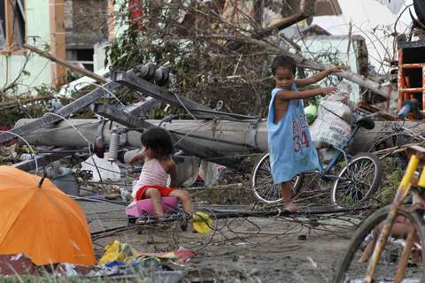 Children play near electric posts which were damaged after super Typhoon Haiyan battered Tacloban city, central Philippines, on Nov. 9.