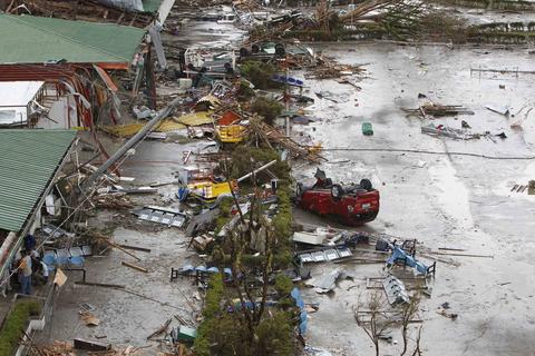 Survivors assess the damage after Typhoon Haiyan battered Tacloban city, central Philippines, on Nov. 9.