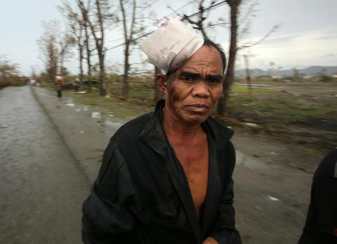 A wounded man walks in the super typhoon devastated city of Tacloban, Leyte province, Philippines, on Nov. 9.