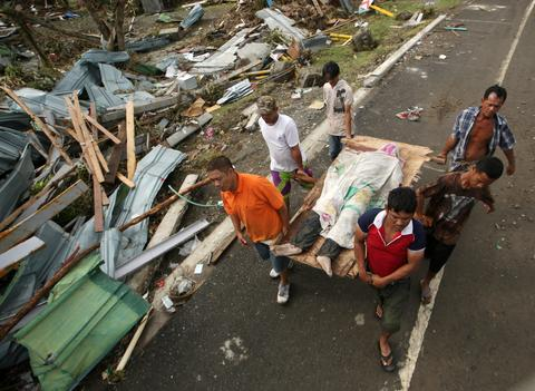 Survivors carry a victim in the super typhoon devastated city of Tacloban, Leyte province, Philippines, on Nov. 9.