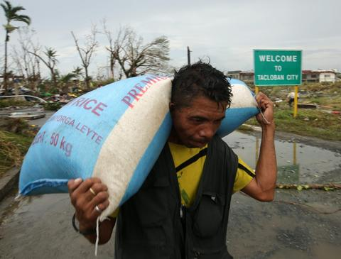 A man carries a sack of rice in the super typhoon devastated city of Tacloban, Leyte province, Philippines, on Nov. 9.