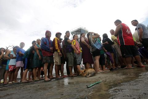 People wait in line for relief goods in the super typhoon devastated city of Tacloban, Leyte province, Philippines, on Nov. 9.