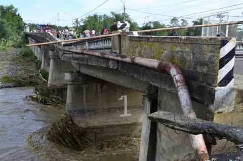 Residents try to cross the damaged Suage bridge after Typhoon Haiyan hit Janiuay, in the Iloilo province in central Philippines, on Nov. 9.