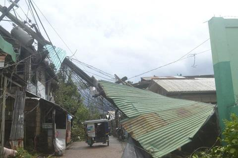 A vehicle passes by collapsed electrical posts and damaged houses after Typhoon Haiyan hit the municipality of Coron, in Palawan province in central Philippines, on Nov. 9.