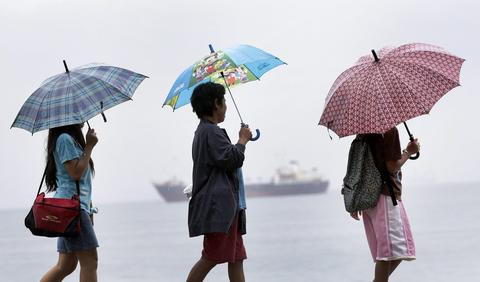 epa03940584 Filipinos women carry their umbrellas during a downpour brought by Typhoon Haiyan in Manila Philippines 08 November 2013. The most powerful cyclone in three decades battered the Philippines killing at least one, forcing hundreds of thousands to flee their homes, and cutting power and communication. Typhoon Haiyan was packing maximum sustained winds of 235 kilometres per hour (kph) and gusts of up to 275 kph as it made landfall over Guiuan town in Eastern Samar province, 650 kilometres south-east of Manila, the national weather bureau said. Other weather organizations placed Haiyan's maximum winds at 315 kph and gusts at 380 kph. More than 125,000 people were evacuated from homes in coastal communities and areas prone to floods or landslides in 22 provinces before Haiyan hit, according to the national disaster relief agency. EPA/DENNIS M. SABANGAN