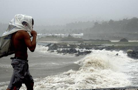 A Filipino walks in front of waves brought by Typhoon Haiyan in Legazpi City, Albay province, Philippines.The most powerful cyclone in three decades battered the Philippines , killing at least three people and displacing over 718,000, disaster relief officials said. More than 718,000 people were evacuated from homes in coastal communities and areas prone to floods or landslides in 29 provinces before Haiyan hit, according to the national disaster relief agency.