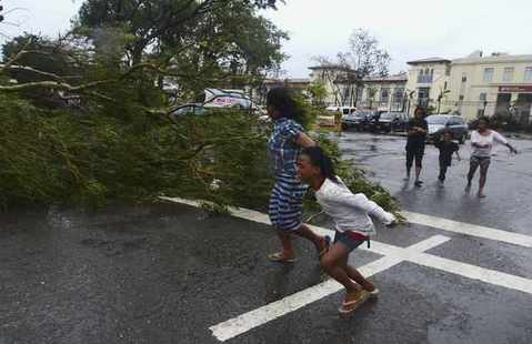 Residents rush to safety past a fallen tree during strong winds brought by Typhoon Haiyan that hit Cebu city, central Philippines November 8, 2013.