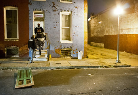 Police enter a residence early Tuesday on the 1700 block of North Bethel Street in East Baltimore as they serve warrants at various locations.