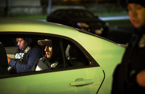 Baltimore police SWAT and special units sit in a car before conducting raids on several homes in East Baltimore.