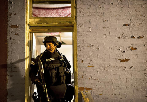 A Baltimore officer stands outside a home in the 1700 block of North Bethel Street in East Baltimore.