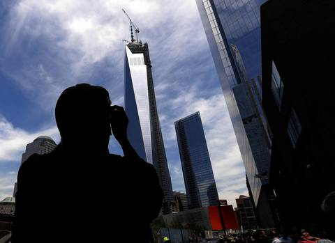 A passerby takes a photo of One World Trade Center as the final section of the spire is placed atop the building.