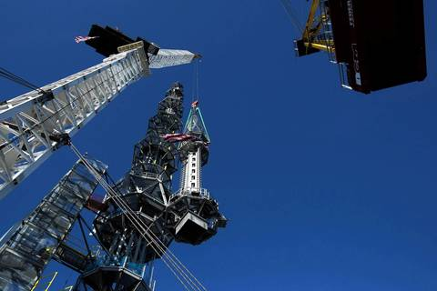The final piece of the building's spire is lifted to the top of the One World Trade Center in New York.