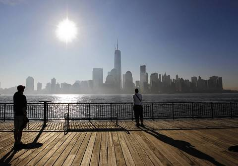 Two men look across the Hudson River from New Jersey at the cityscape of New York, after the One World Trade Center had the final piece of its spire attached.