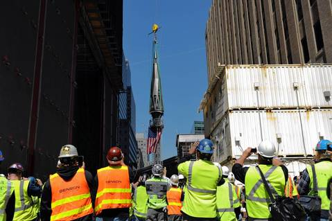 Construction workers watch as the final sections of the spire is raised to the top of One World Trade Center in New York to a temporary work platform atop the structure. Ironworkers will install the sections at a later date and when complete, One WTC will stand 1,776 feet (541 meters) high, making it the tallest building in the Western Hemisphere.