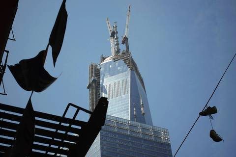 The final pieces of the spire for One World Trade Center are hoisted to its final position atop the tower.