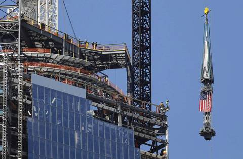 The final section of the spire that will top off One World Trade Center is raised past iron workers to the top of the building.