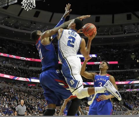 Duke guard Quinn Cook is fouled by Kansas center Joel Embiid.