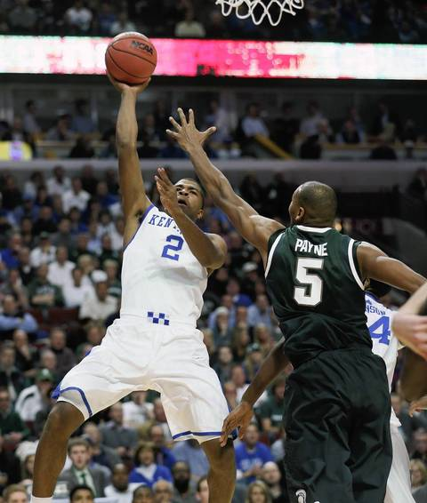 Kentucky guard Aaron Harrison shoots over Michigan State center Adreian Payne.