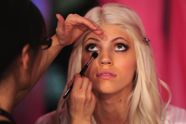 A model gets ready backstage prior to the 2013 Victoria's Secret Fashion Show at the Lexington Avenue Armory on November 13, 2013 in New York.
