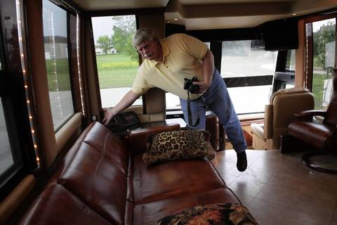 A prospective buyer reclines a couch in Rita Crundwell's motor home at the Oak Creek Police Department in Oak Creek, Wisconsin.