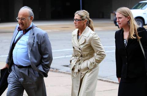 Rita Crundwell, center, comptroller and treasurer for three decades in Dixon, Ill., and charged with one count of wire fraud, leaves the federal courthouse in Rockford on Wednesday. Crundwell allegedly took $53 million from the small city in a decades-long scam to finance her Dixon ranch.